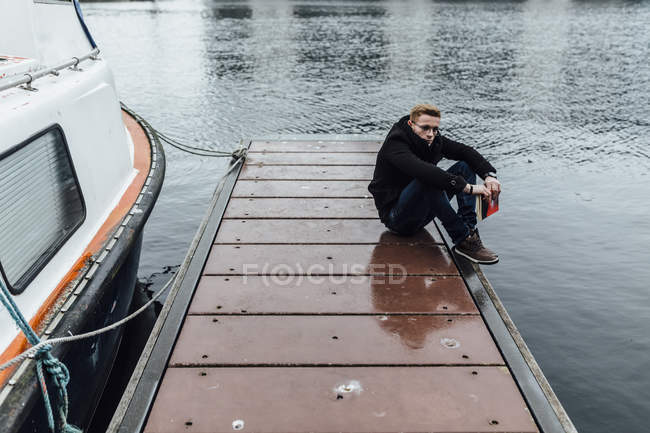 Young man with book cowering on a jetty in winter — Stock Photo