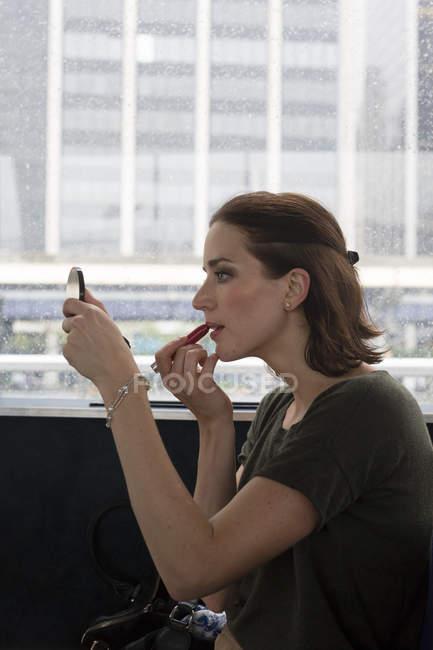 Young woman applying make up — Stock Photo