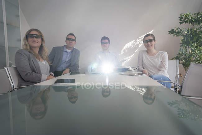 Quattro colleghi con occhiali 3d presenti a una presentazione con proiettore in sala conferenze — Foto stock
