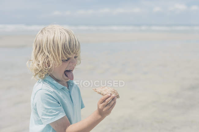 Белокурый мальчик на пляже гримасит и держит краба — стоковое фото