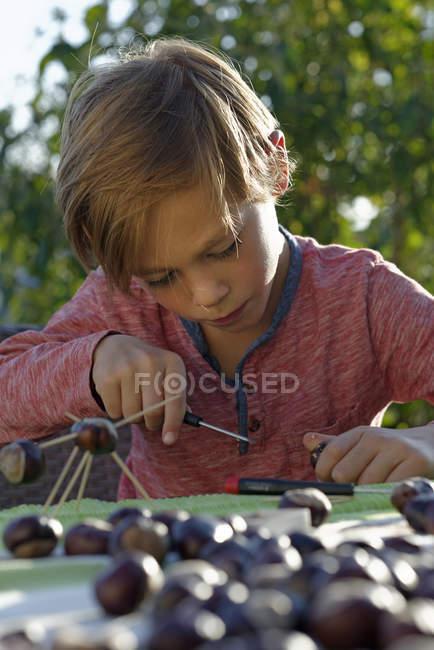 Little boy tinkering chestnut figurines — Stock Photo