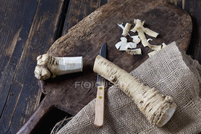 Corte e rábano pelado na placa de madeira e juta — Fotografia de Stock
