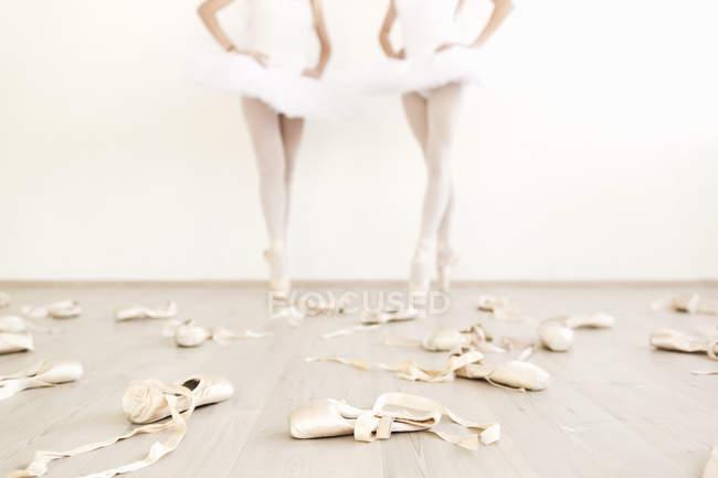 Chaussures de ballet éparpillés sur le sol avec deux danseurs à l'arrière-plan — Photo de stock