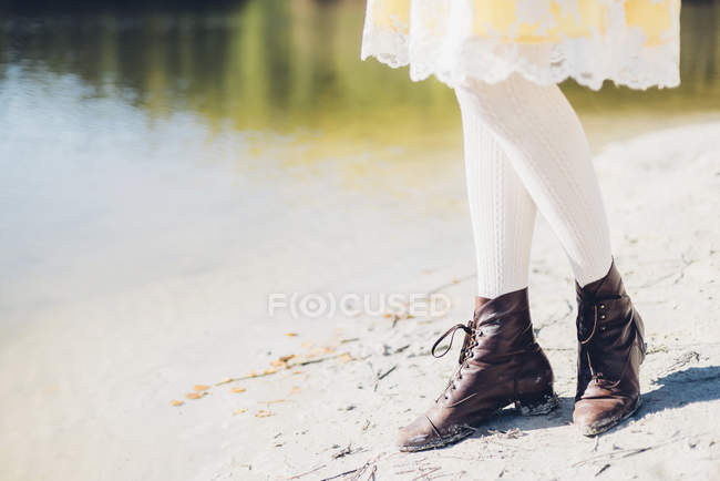 Legs of old-fashioned styled woman at water's edge — Stock Photo