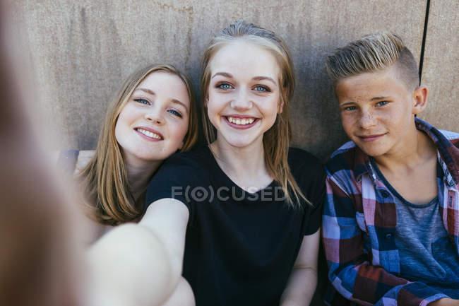 Drei verspielte Teenager im freien unter einem selfie — Stockfoto