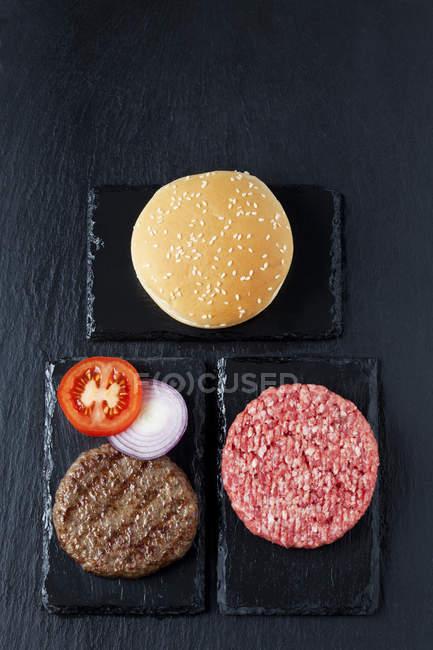 Vista superiore di polpette di carne con pomodoro, anelli di cipolla e panino — Foto stock