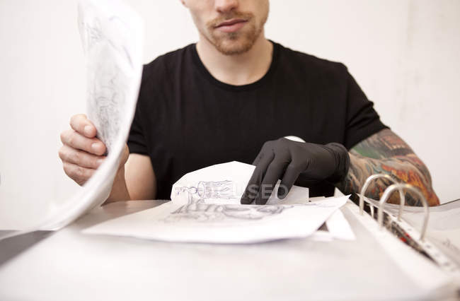 Tattooist with drafts in his tattoo studio — Stock Photo