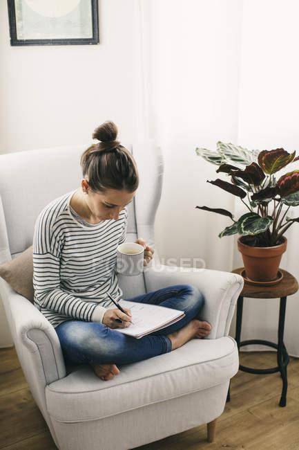 Donna seduta in poltrona e scrivere sul blocco note — Foto stock
