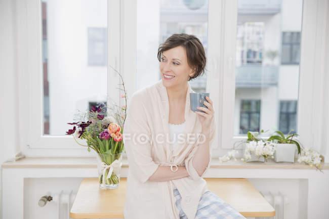 Lächelnde Frau zu Hause sitzen am Tisch halten Tasse — Stockfoto