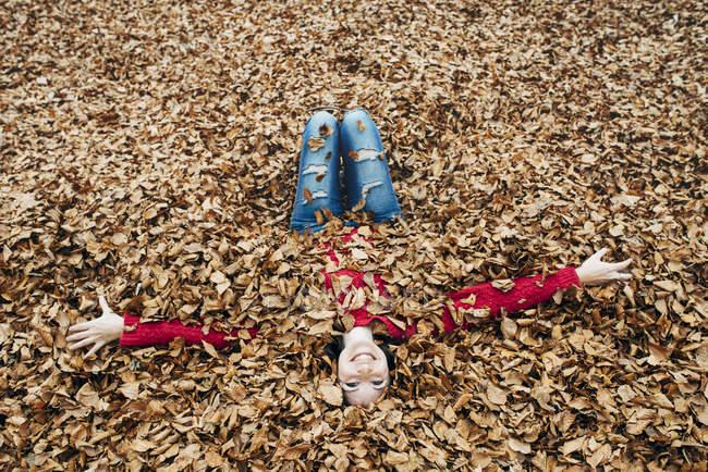 Frau mit ausgestreckten Armen auf mit Herbstblättern bedecktem Waldboden liegend — Stockfoto