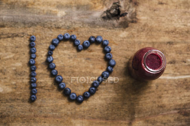 Smoothie de mirtilo em garrafa com Eu amo escrever de mirtilos em madeira — Fotografia de Stock