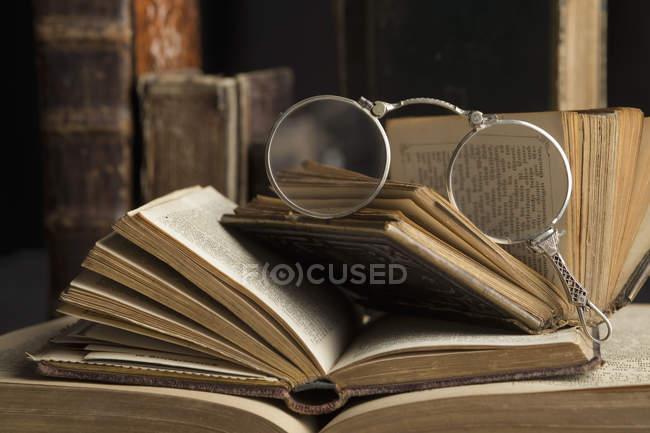Lorgnette sur pile de livres anciens, gros plan — Photo de stock