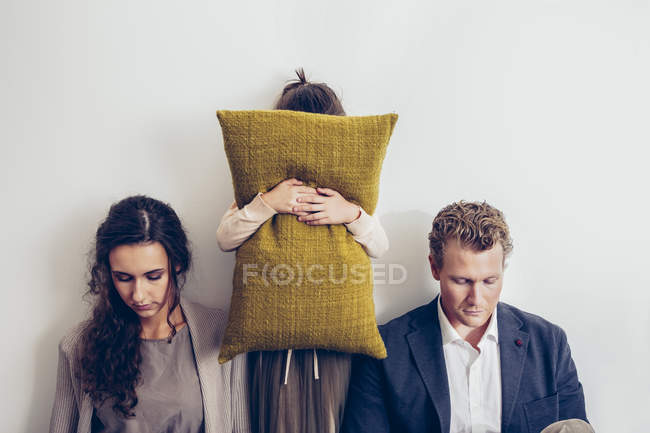Couple having relationship conflict with their daughter hiding her face behind cushion — Stock Photo