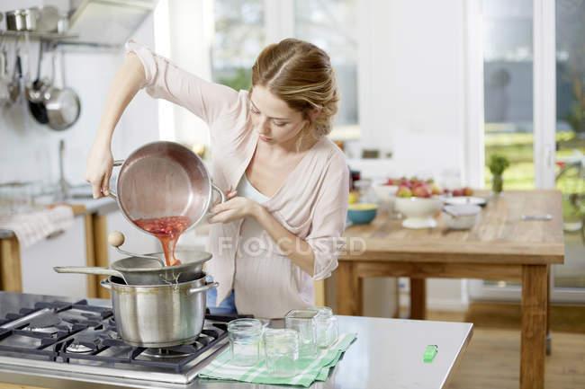 Mujer joven haciendo mermelada en la cocina - foto de stock