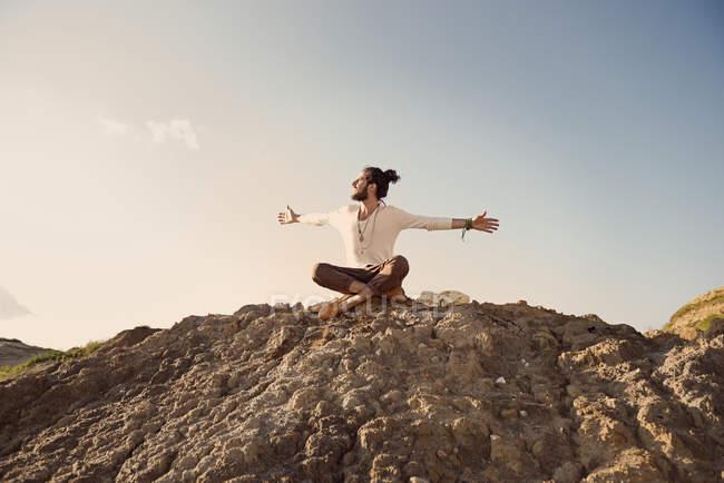 Человек, сидящий на холме с распростертыми объятиями — стоковое фото