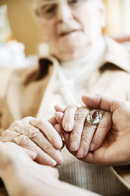 Adult daughter holding hands of her mother with Alzheimer's disease, close-up — Stock Photo