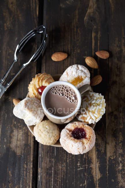 Различные виды итальянских миндальное печенье и чашку какао на темное дерево — стоковое фото