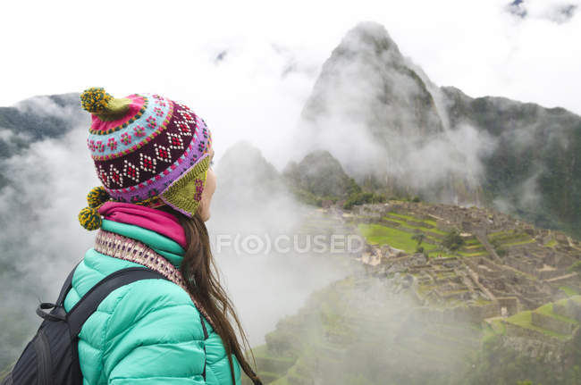 Peru, woman enjoying Machu Picchu before sunrise with the ruins surrounded by fog — Stock Photo