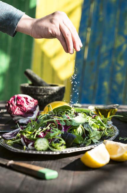 Blick auf Salat mit Kopfsalat, Rucola, Spinat und Kräutern würzen Hand abgeschnitten — Stockfoto