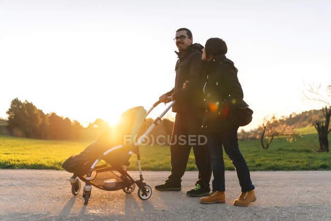 Пару на прогулянку з свою дитину в колясці на заході сонця — стокове фото