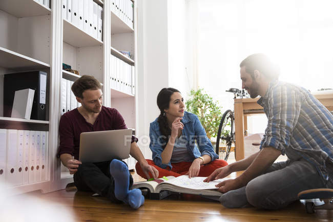 Three creative business people sitting on the floor discussing — Stock Photo
