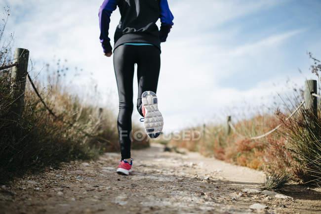 Вид сзади на женщину, бегущую на улице — стоковое фото