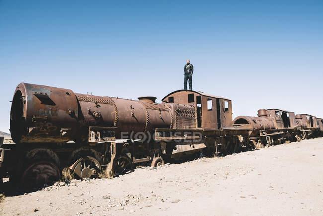 Bolivia, Uyuni tren cementerio, hombre de pie en la cabina de un tren oxidado viejo - foto de stock