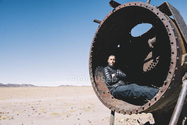 Bolivia, cementerio de trenes Uyuni, hombre relajante dentro de un antiguo depósito de tren - foto de stock