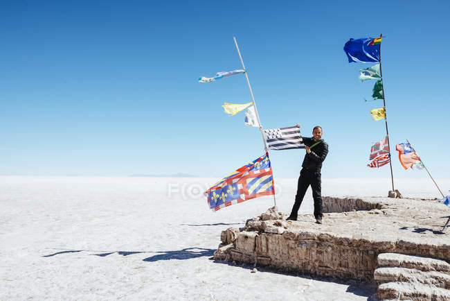 Bolivien, Atacama, Altiplano, Salar de Uyuni, Fahnen aus allen Ländern, Mann hält eine Fahne — Stockfoto