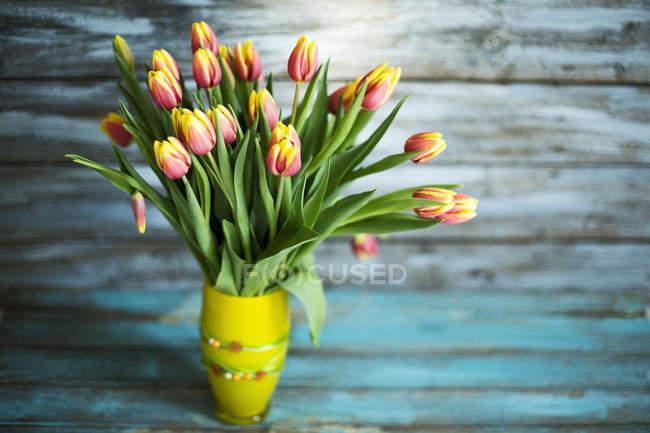 Yellow Flower vase of tulips on blue shabby wooden background — Stock Photo