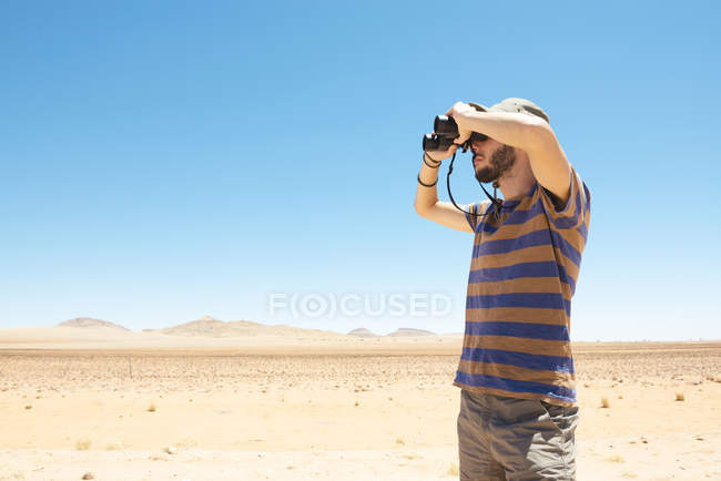 Namibia, Namib deserto, uomo con cappello con binocolo per distogliere lo sguardo — Foto stock