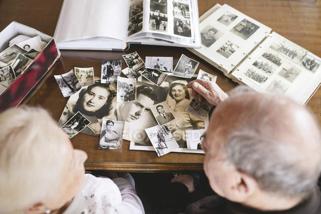 Senior couple with photo albums and old photographies at home — Stock Photo