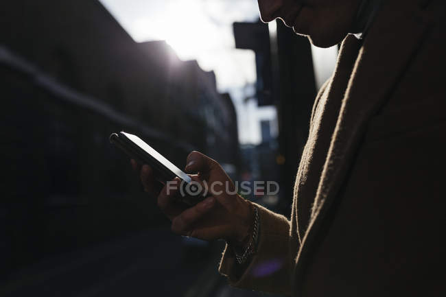 Man looking on cell phone in the city — Stock Photo