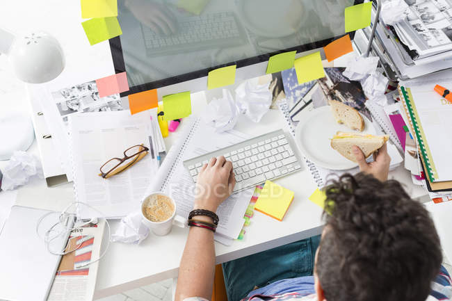 Young man sitting at messy office desk eating a sandwich — Stock Photo