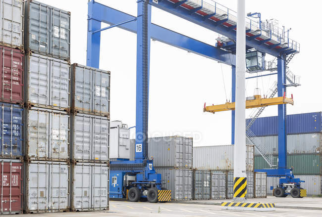 Industrial containers and crane at harbor — Stock Photo