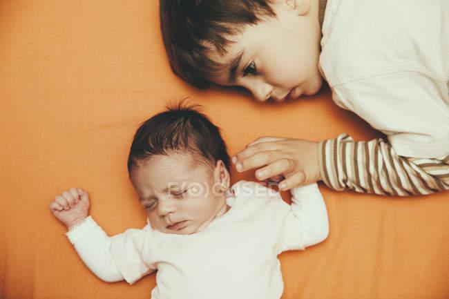 Новорожденный ребенок девочка и брат, лежа на кровати — стоковое фото