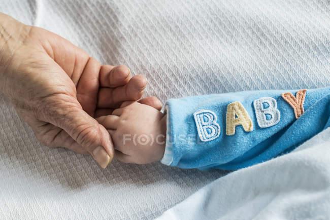 Обрезанный вид пожилой женщины и ребенка, держащихся за руки — стоковое фото
