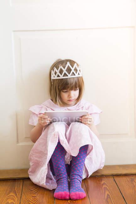 Chica vestida como una princesa mirando tableta digital - foto de stock