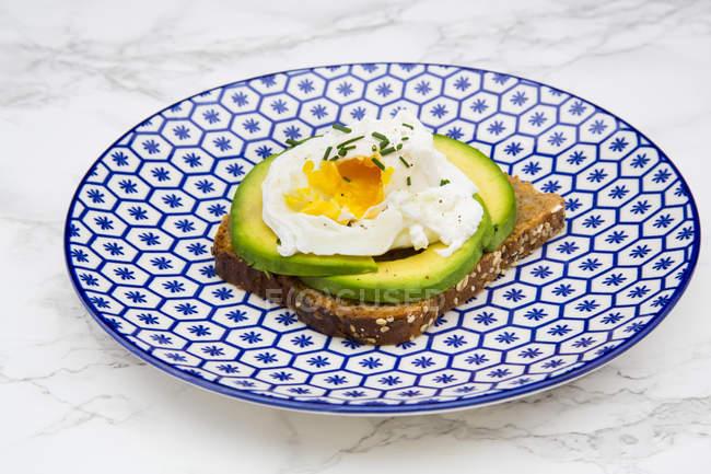 Скибочки хліб з непросіяного борошна з скибочками авокадо і вареними яйцями на тарілку — стокове фото