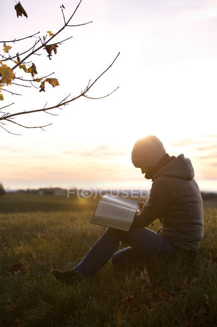 Woman reading a book on an autumnal meadow at sunrise — Stock Photo