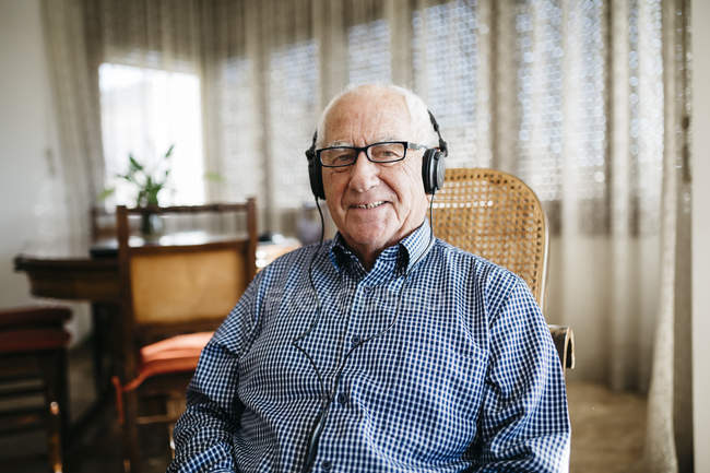 Senior man listening music with headphones — Stock Photo