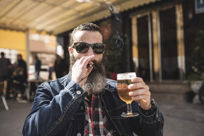 Man smoking and drinking beer — Stock Photo