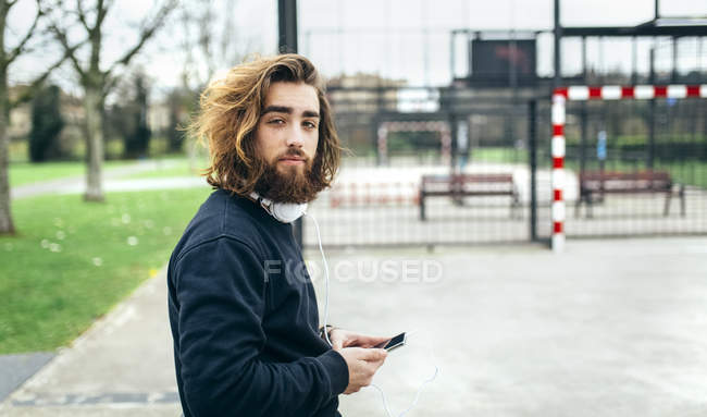 Portrait of bearded young man with smartphone and headphones — Stock Photo