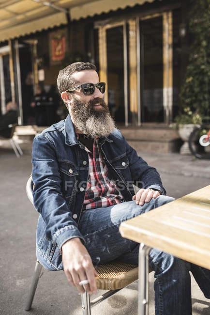 Man smoking at outdoor cafe — Stock Photo