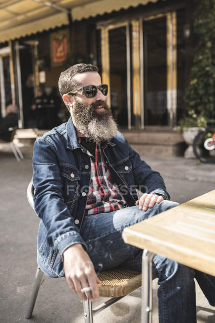 Man smoking at outdoor cafe — Stock Photo
