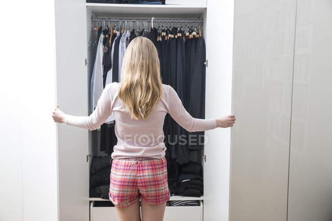 Visão traseira da jovem mulher olhando para a roupa em seu guarda-roupa — Fotografia de Stock