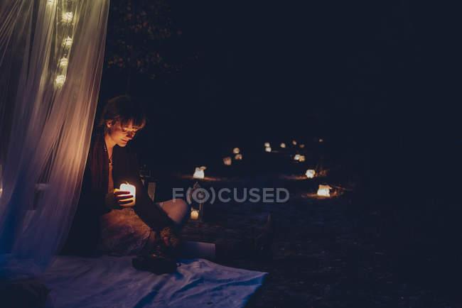 Mulher em um acampamento romântico iluminado por luzes de vela na natureza — Fotografia de Stock