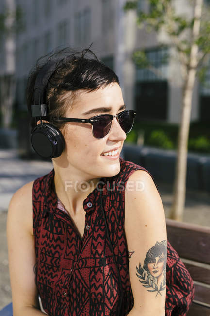 Ritratto di giovane donna tatuata con cuffie e occhiali da sole — Foto stock