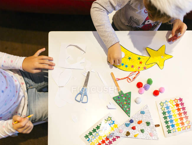 Two little girls tinkering Christmas decoration — Stock Photo