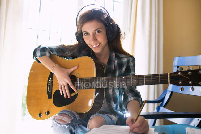 Smiling young woman with headphones, guitar and music sheet — Stock Photo
